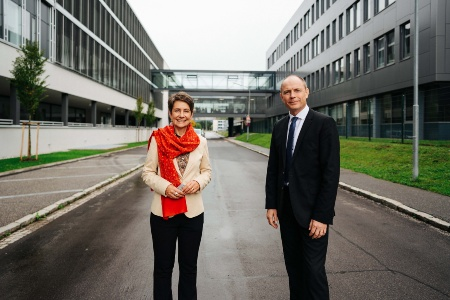 Infineon Austria CEO Sabine Herlitschka and Infineon Austria CFO Oliver Heinrich in the Siemensstrasse, in front of the new building and transitions to the existing buildings.