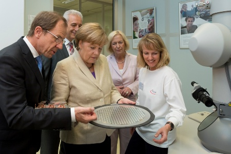 CEO Reinhard Ploss explains German Chancellor Angela Merkel the structure of a power chip on a 300mm thinwafer F.l.t.r: Dr. Reinhard Ploss (CEO Infineon Technologies AG), Stanislaw Tillich (Prime Minister of Saxony), Dr. Angela Merkel (Chancellor of Germany), Prof. Dr. Johanna Wanka (Federal Minister of Education and Research), Infineon employee.