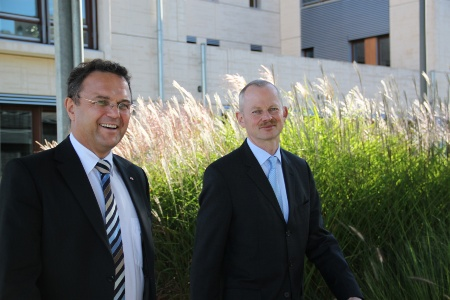 The German Federal Minister of the Interior, Dr. Hans-Peter Friedrich (left), and Peter Bauer, CEO of Infineon Technologies AG, at Infineon's headquarters in Neubiberg near Munich on their way to Infineon's security laboratories.