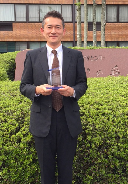 Natsuki Tokubuchi, Head of the Automotive business at Infineon Technologies Japan, holding Toyota Hirose Plant Quality Award