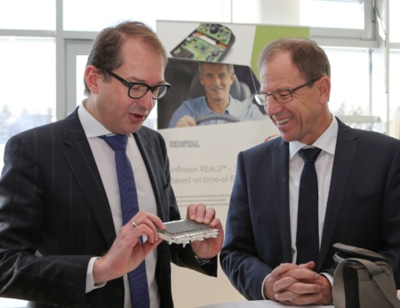 Infineon's CEO Dr. Reinhard Ploss (right) demonstrates Alexander Dobrindt, German Federal Minister of Transport and Digital Infrastructure, a power module used for motor control in electric vehicles.